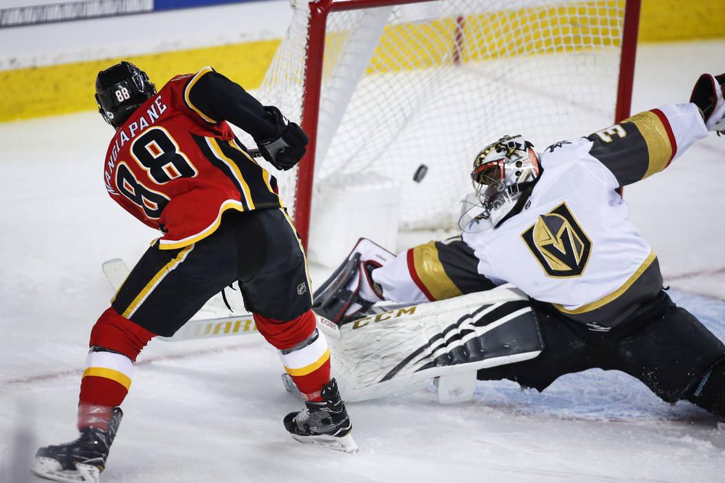 El portero de los Golden Knights de Vegas, Malcolm Subban, a la derecha, deja entrar un gol de Andrew Mangiapane de los Calgary Flames durante el primer período de acción de hockey de la NHL en ...
