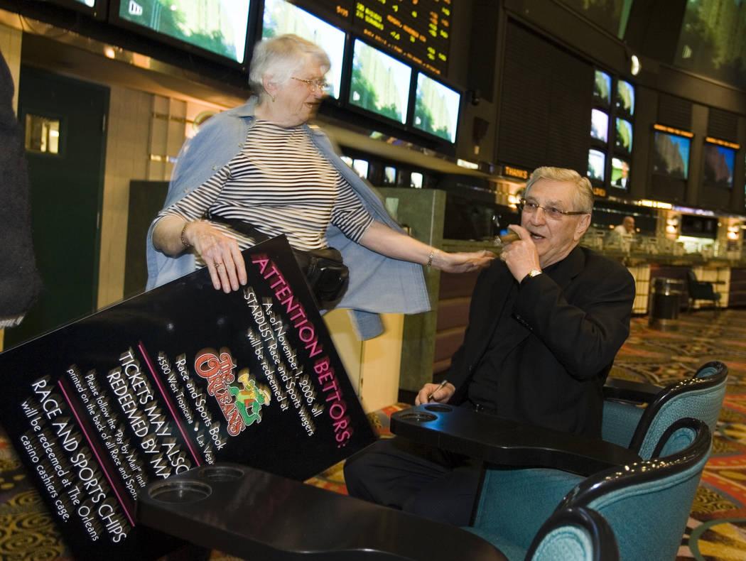 La patrona de veinte años, Joyce Lindsay, de Manitoba, Canadá, le pide a Bill Boyd, presidente de Boyd Gaming, que autografíe un letrero de recuerdo en el directorio de Stardust Race and Sports ...