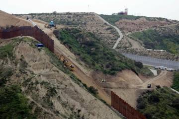Los equipos de construcción reemplazan una sección del muro primario que separa a San Diego, arriba a la derecha, y Tijuana, México, abajo a la izquierda, el lunes 11 de marzo de 2019, visto de ...