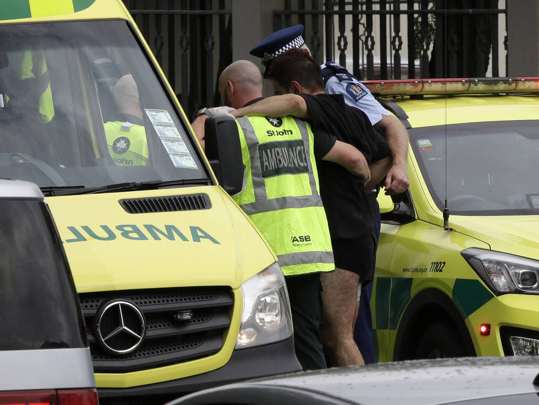 La policía y el personal de ambulancias ayudan a un hombre herido desde afuera de una mezquita en el centro de Christchurch, Nueva Zelanda, el viernes 15 de marzo de 2019. (AP Photo / Mark Baker)