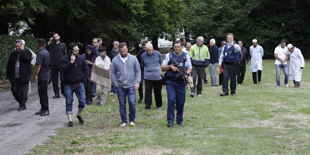 La policía escolta a testigos que se alejan de una mezquita en el centro de Christchurch, Nueva Zelanda, el viernes 15 de marzo de 2019. (AP Photo / Mark Baker)