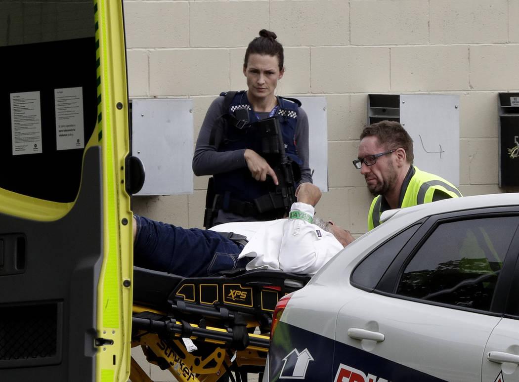 Un oficial de policía armado observa a un personal de ambulancia que asiste a un hombre de una mezquita en el centro de Christchurch, Nueva Zelanda, el viernes 15 de marzo de 2019. (AP Photo / Ma ...