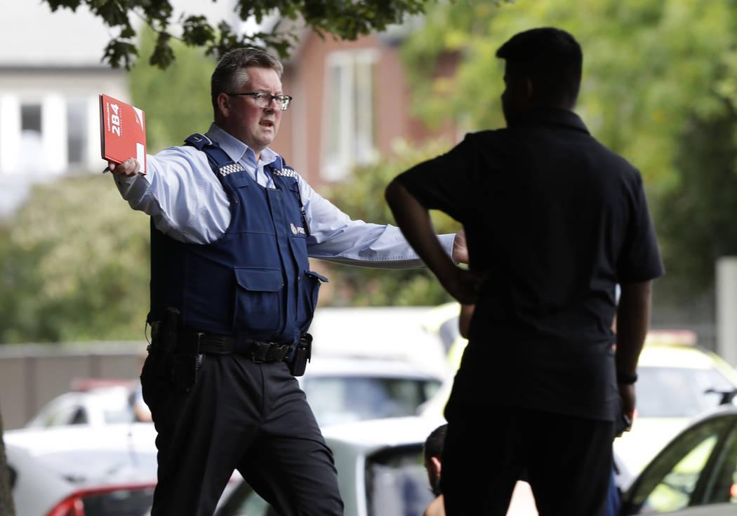 Un oficial de policía intenta alejar a las personas del otro lado de la carretera de una mezquita en el centro de Christchurch, Nueva Zelanda, el viernes 15 de marzo de 2019. (AP Photo / Mark Baker)