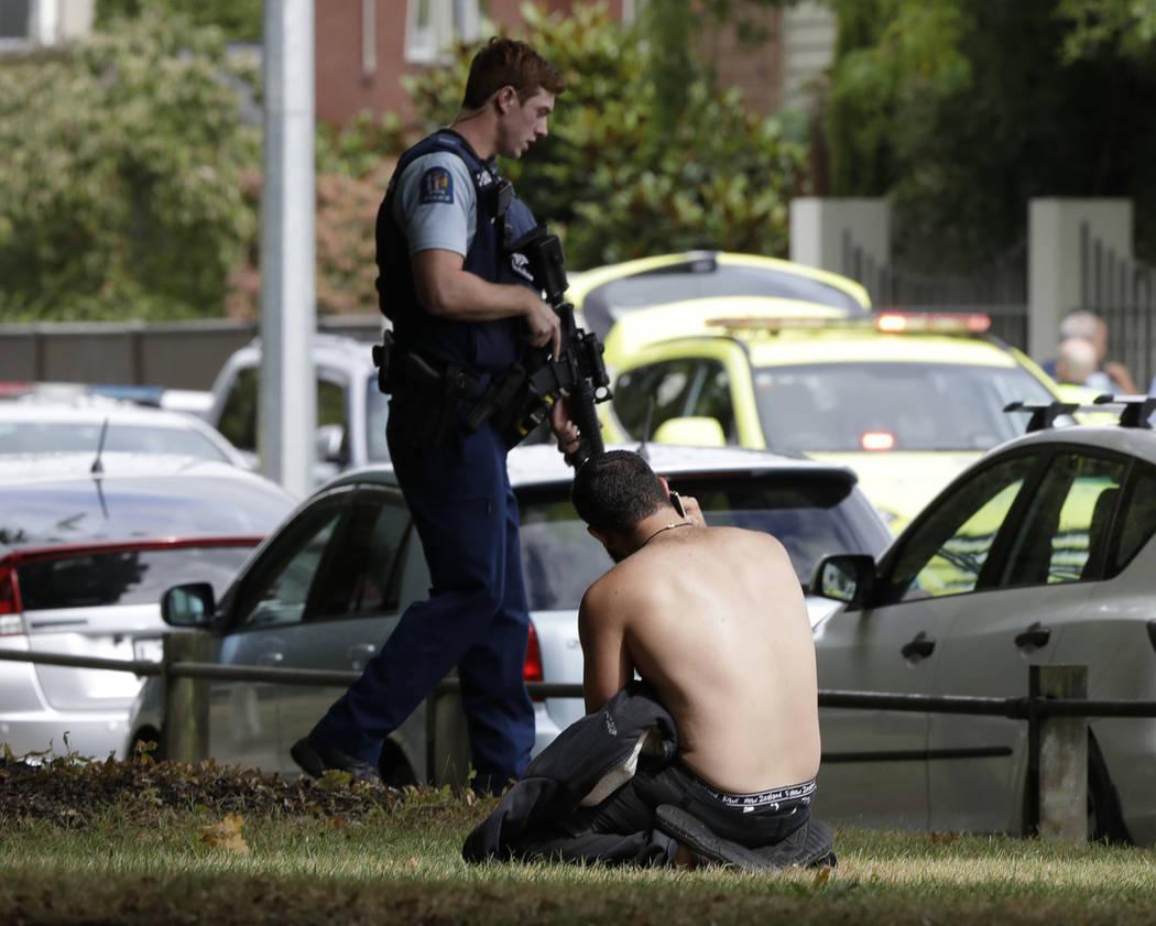 Un hombre descansa en el suelo mientras habla por su teléfono móvil al otro lado de la carretera de la mezquita en el centro de Christchurch, Nueva Zelanda, viernes 15 de marzo de 2019. (AP Phot ...