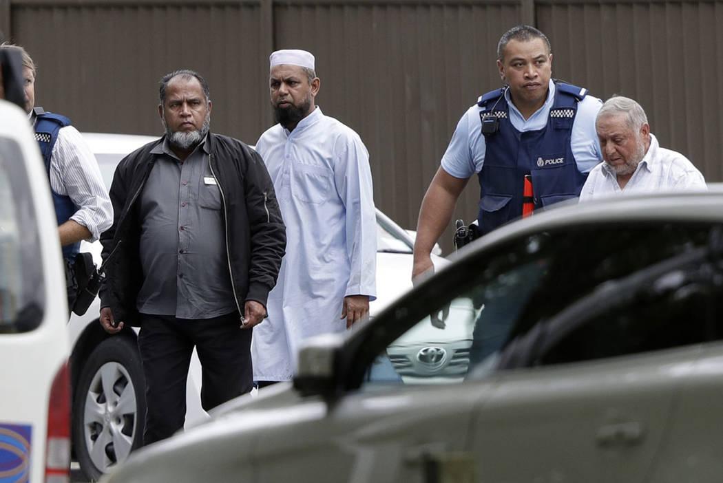La policía escolta a hombres de una mezquita en el centro de Christchurch, Nueva Zelanda, el viernes 15 de marzo de 2019. (Foto AP / Mark Baker)
