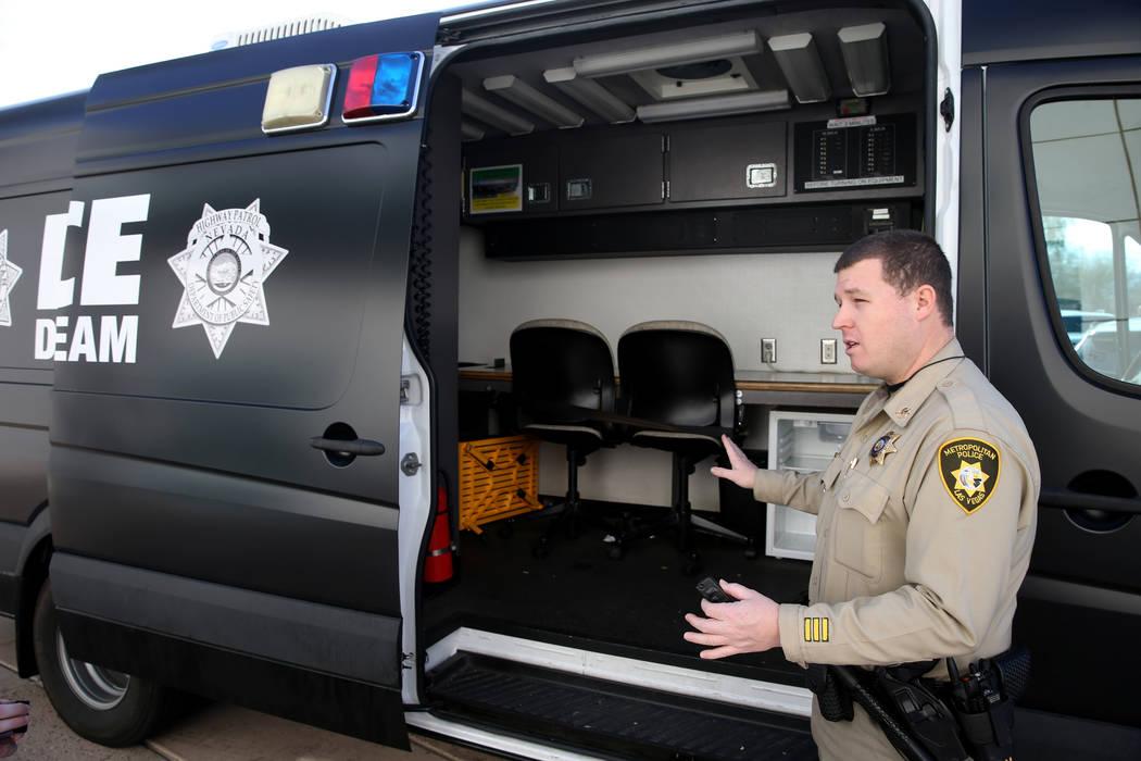 El oficial de tránsito del Departamento de Policía Metropolitana, Mike Thiele, muestra la camioneta utilizada para el procesamiento y el transporte de los supuestos conductores incapacitados por ...