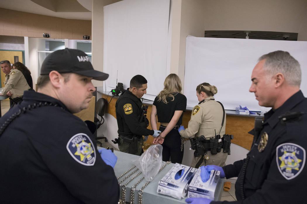El agente Johnny Patino, segundo desde la izquierda, y el Oficial de la Policía Metropolitana B. Muenzenmeyer, segundo desde la derecha, procesan a un conductor con discapacidad sospechada en la ...