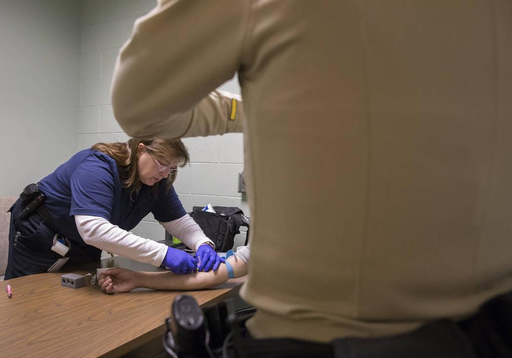 """La Dra. Katharine York, a la izquierda, extrae sangre de un supuesto conductor incapacitado en la Oficina de Tránsito del Metro como parte de una """"campaña de DUI"""" el jueves 14 de marzo de 2019, ..."""