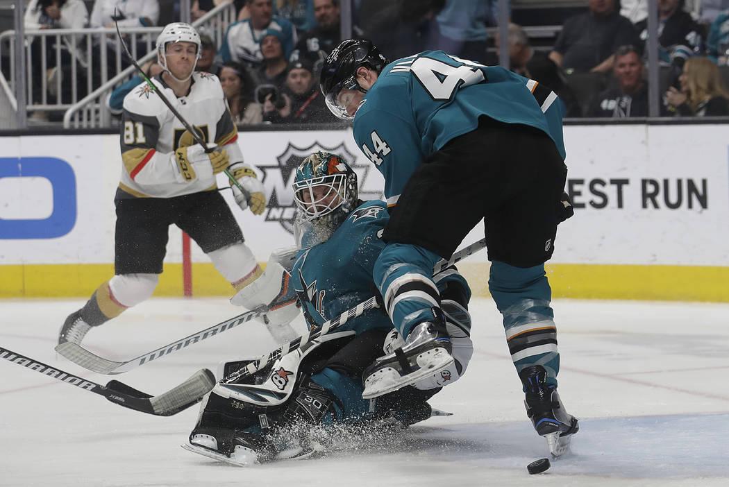 El portero Aaron Dell, centro, y el defensa Marc-Edouard Vlasic (44) de los San José Sharks, buscan el puck frente al centro Jonathan Marchessault (81) de los Golden Knights de Las Vegas durante ...