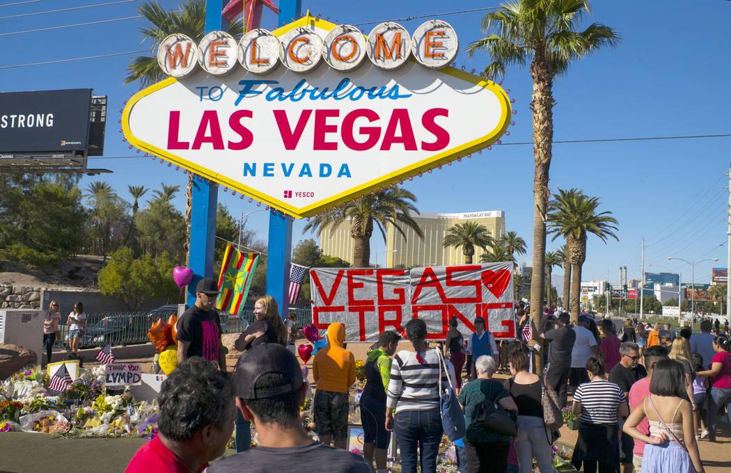 """El sábado 7 de octubre de 2017, la gente visita un monumento improvisado para víctimas del tiroteo masivo del 1 de octubre cerca del cartel de """"Bienvenido a Las Vegas"""". Chase Stevens Las Vegas R ..."""