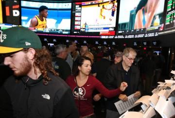 Fans, incluyendo a Ivette Abramyan, al centro, de Jacksonville, Florida, se alinearon para hacer sus apuestas durante el primer día del torneo de baloncesto de la NCAA en la casa de apuestas de W ...