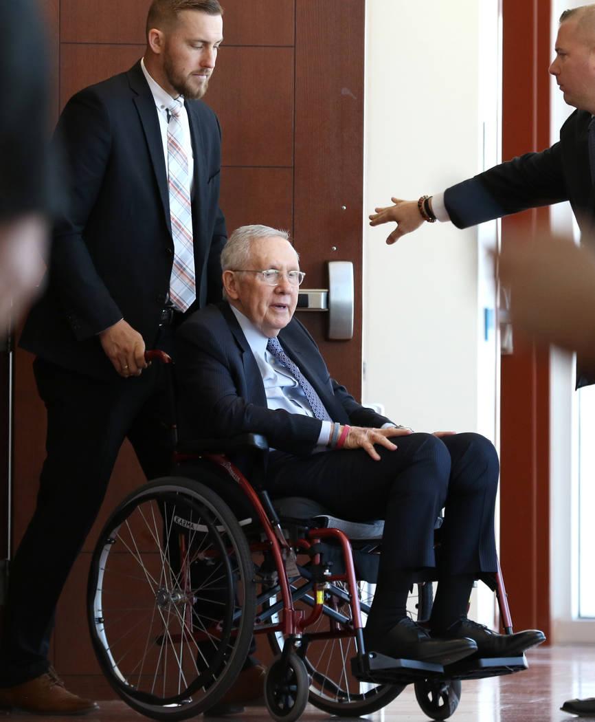 El ex senador estadounidense Harry Reid, quien demandó a los creadores de una banda de ejercicio después de lesionarse el ojo, abandona la sala de audiencias en una silla de ruedas después de a ...