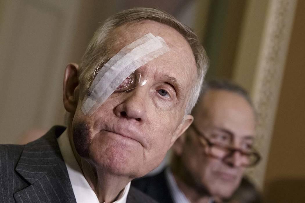 El entonces líder de la minoría en el Senado, Harry Reid, de Nevada, conversa con reporteros en Capitol Hill en Washington, DC, el 22 de enero de 2015, por primera vez después de sufrir una les ...