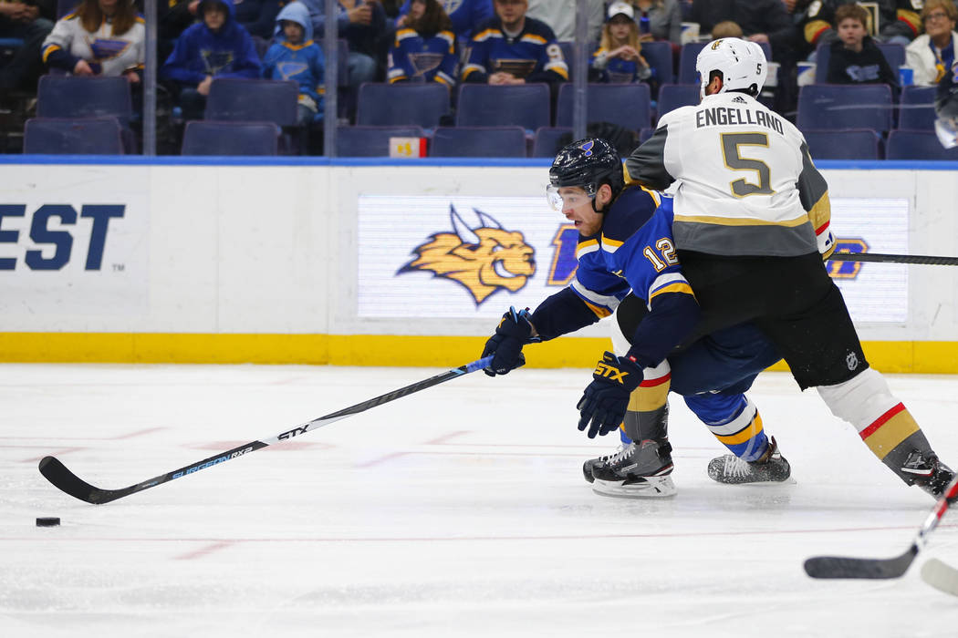Alex Pietrangelo (27) de St. Louis Blues, mantiene a Deryk Engelland (5) de los Golden Knights de Vegas fuera del alcance del puck durante el primer período de un juego de hockey de la NHL el lun ...