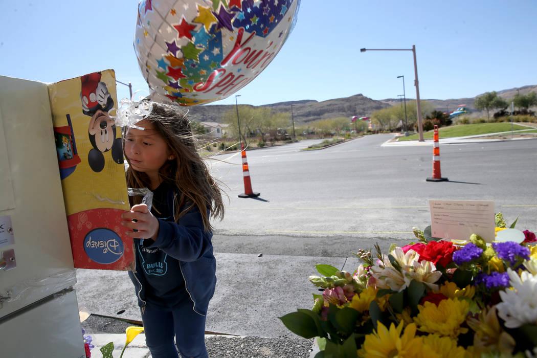 Evelyn Yoshimori, de 7 años, firma un memorial en South Fort Apache Road en Faiss Park en Las ...