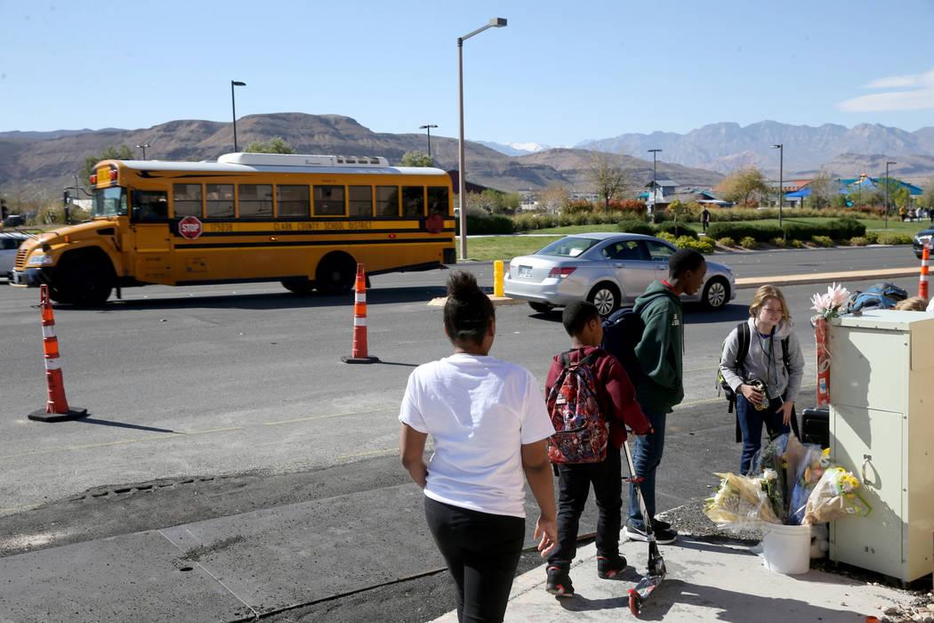 La gente visita un monumento conmemorativo en la intersección de South Fort Apache Road y West ...