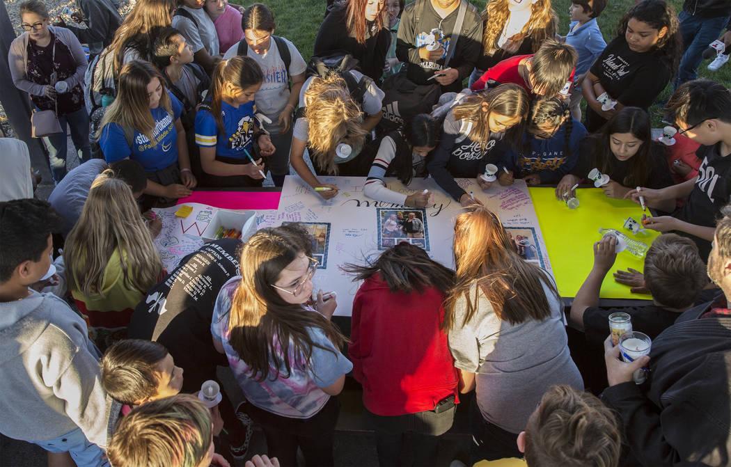Un gran grupo de niños firman un cartel que honra la memoria de Jonathan Smith, de 12 años, d ...