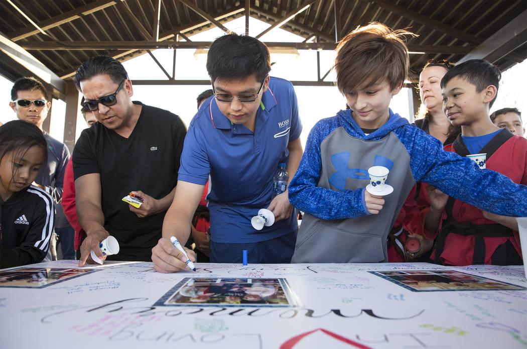 Los asistentes firman un cartel en honor a la memoria de Jonathan Smith, de 12 años, durante u ...