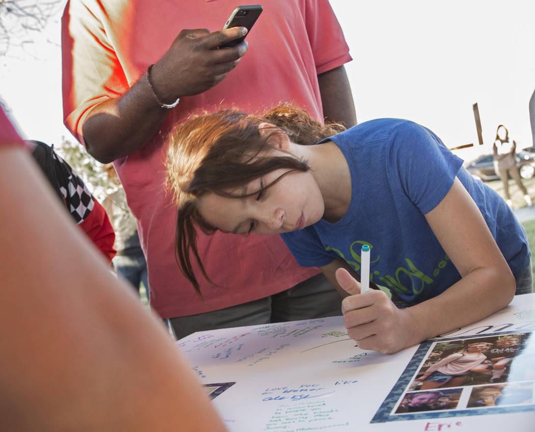Sayuri Reyes, de 8 años, firma un cartel en honor a Jonathan Smith, de 12 años, durante un ve ...