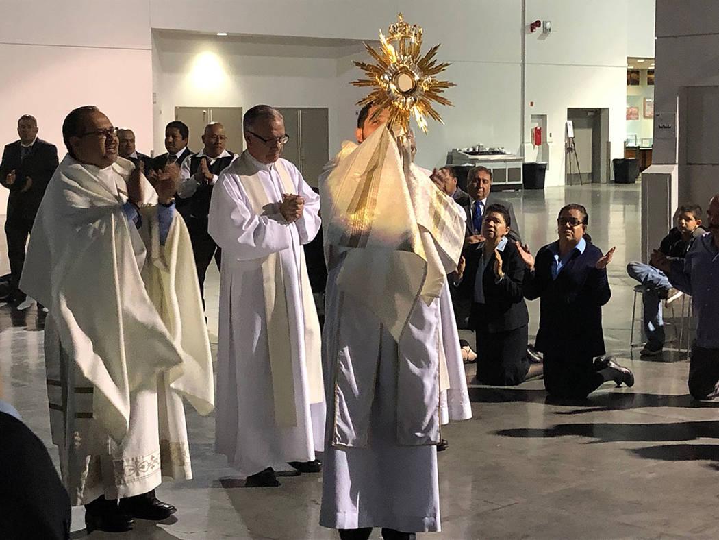 El reverendo Juan P. Mantilla levanta el Santísimo. Al centro el padre Gregorio León, al inic ...