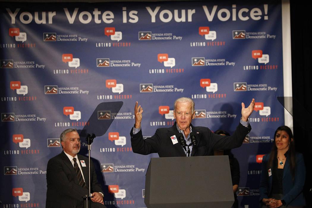 El vicepresidente Joe Biden, en el centro, habla durante un evento de votación, con Henry R. M ...