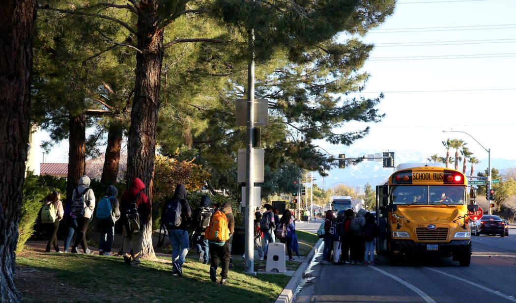 Los estudiantes suben al autobús escolar en Soaring Gulls Drive cerca de Cheyenne Avenue en De ...