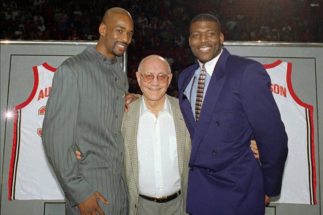 El ex entrenador principal de baloncesto de la UNLV, Jerry Tarkanian, centro, posa con dos de s ...