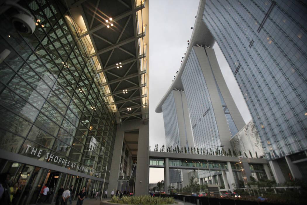 La gente camina cerca de la fachada del resort Marina Bay Sands el 23 de junio de 2010. (Wong M ...