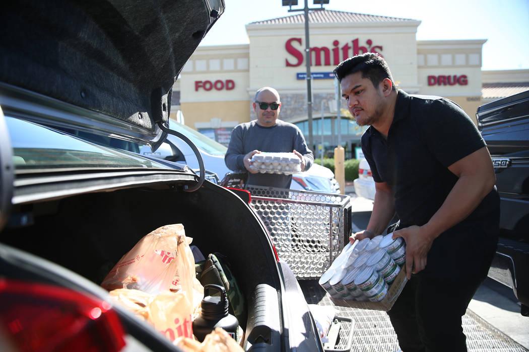 Michael Pabua, a la derecha, con su padre Jun, carga su automóvil con comestibles después de ...