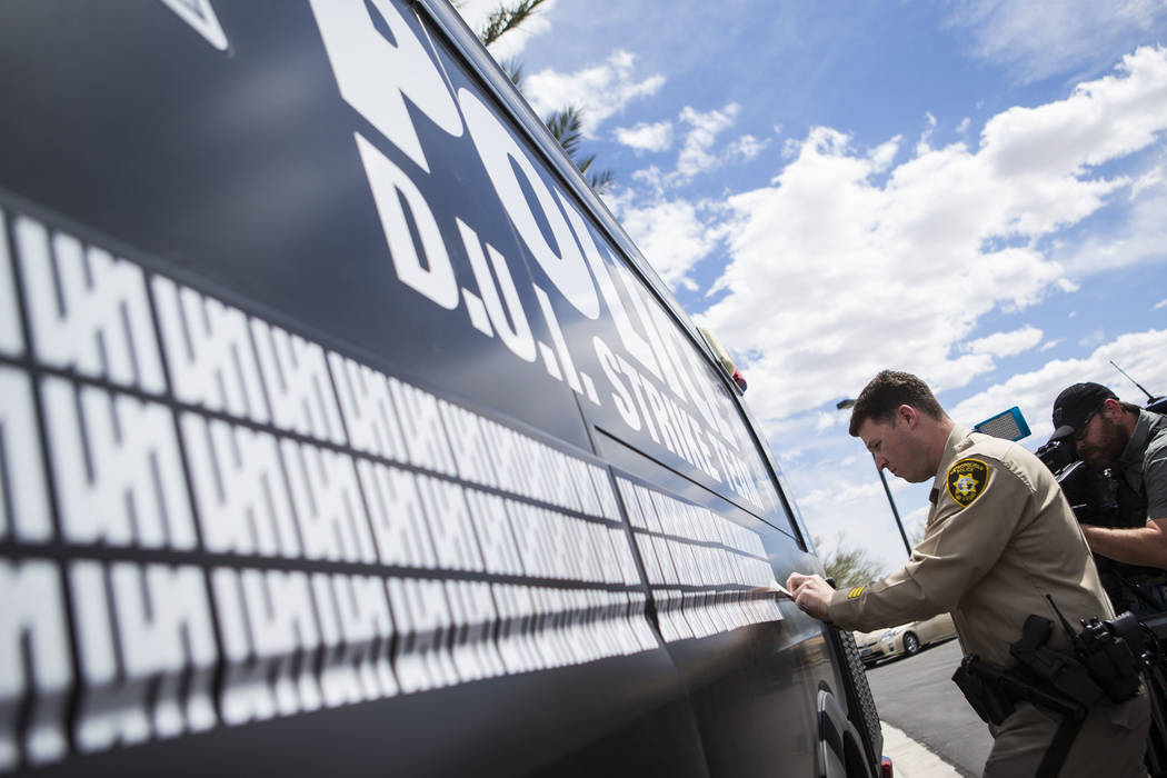 Metropolitan Police Department traffic officer Mike Thiele adds a marking to indicate 500 arres ...