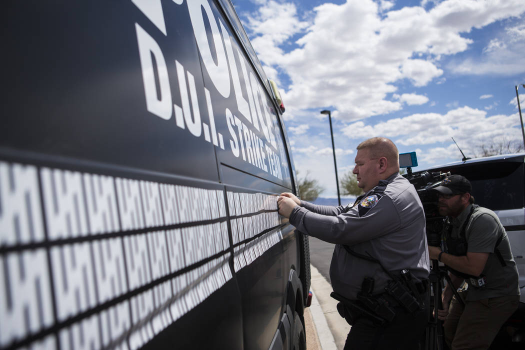 Nevada Highway Patrol trooper Dan Slattery adds a marking to indicate 500 arrests by the DUI St ...