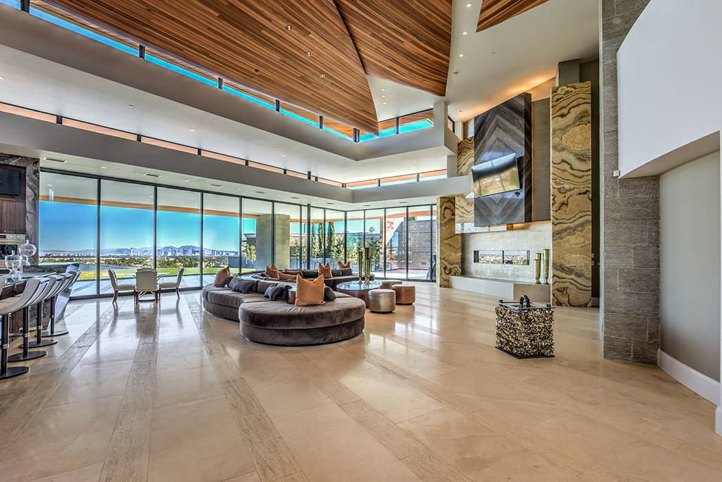 La casa tiene una gran cantidad de ventanas de piso a techo para capturar vistas panorámicas d ...