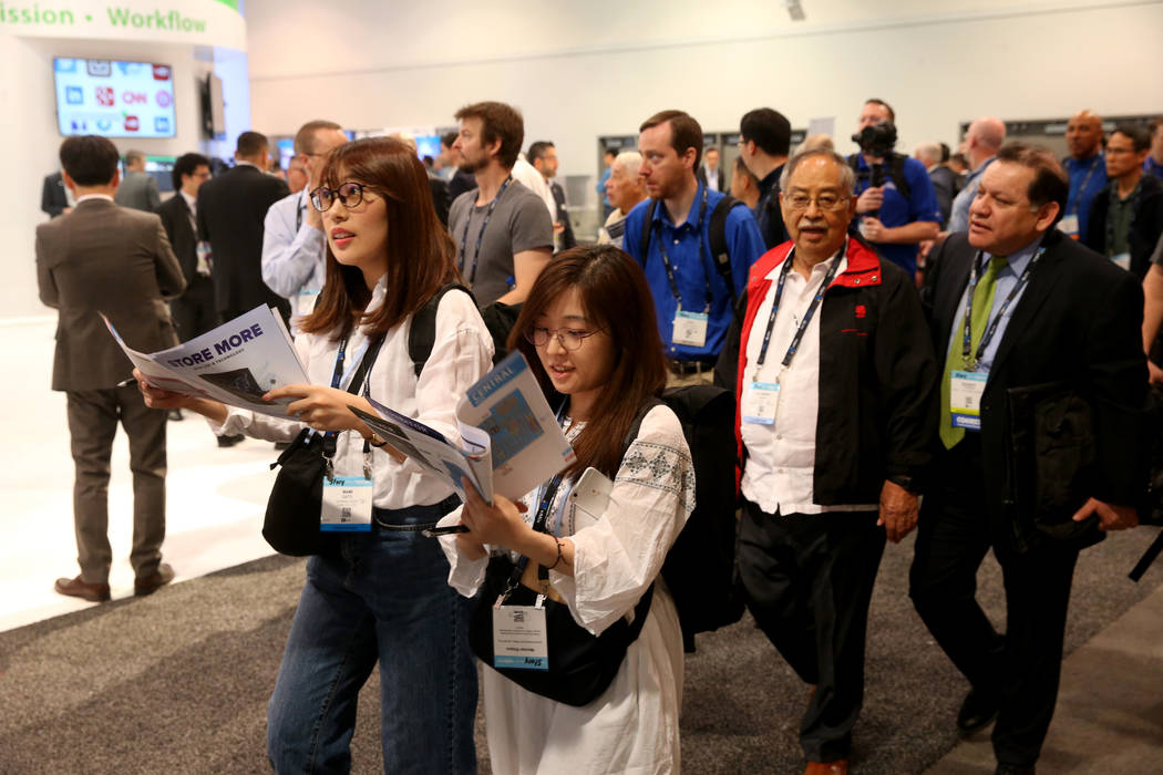 Los asistentes a la convención llegan a la sala de exposiciones el día de la inauguración de ...