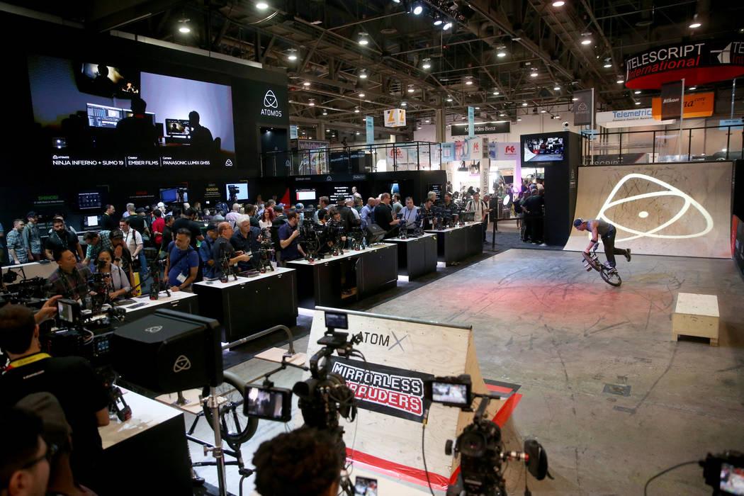 Un ciclista profesional de BMX hace trucos para que los asistentes a la convención puedan ver ...