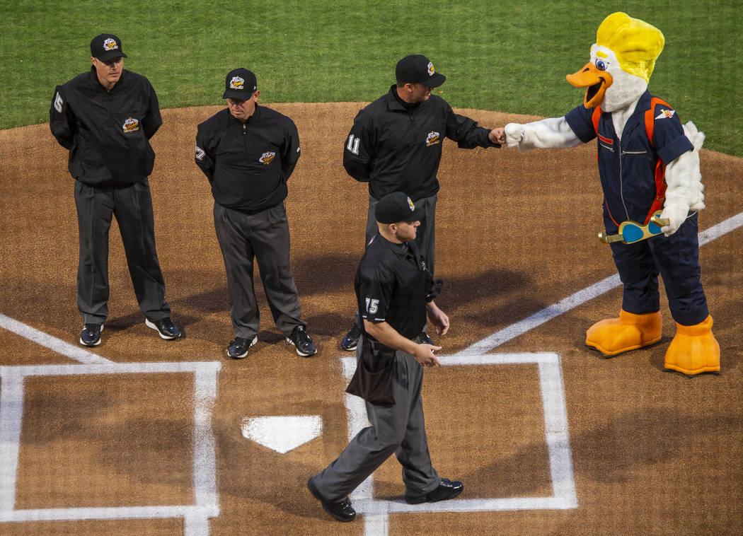 Los árbitros se reúnen en el home plate y son recibidos por Spruce antes del inicio de la ape ...