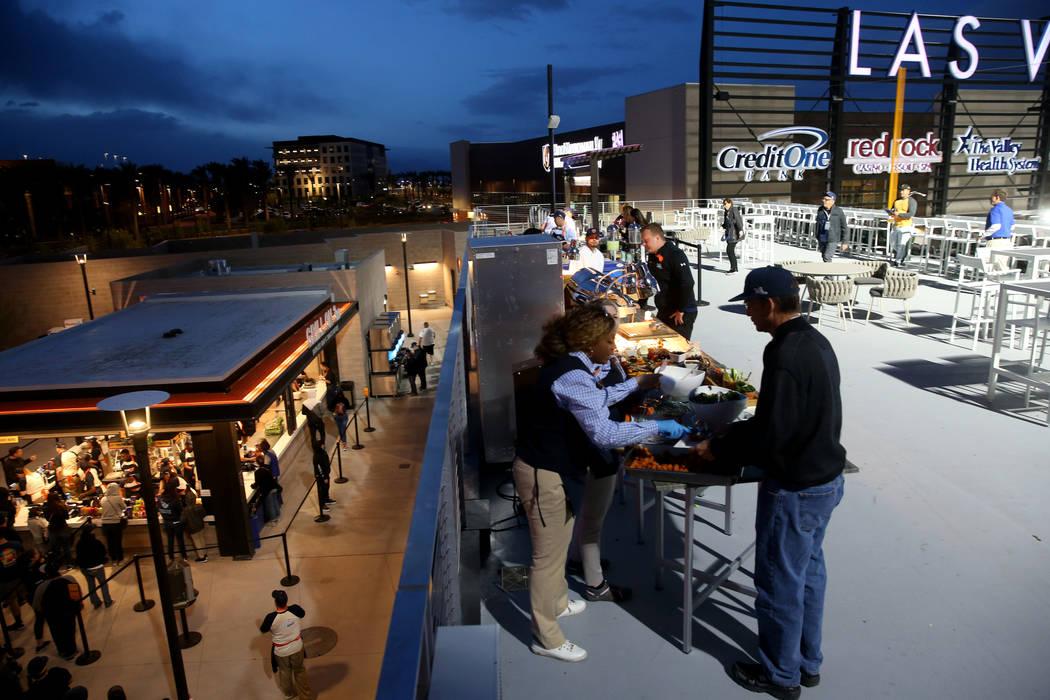 Fans toman comida en la primer noche de apertura de los Aviators de Las Vegas en el estadio de ...