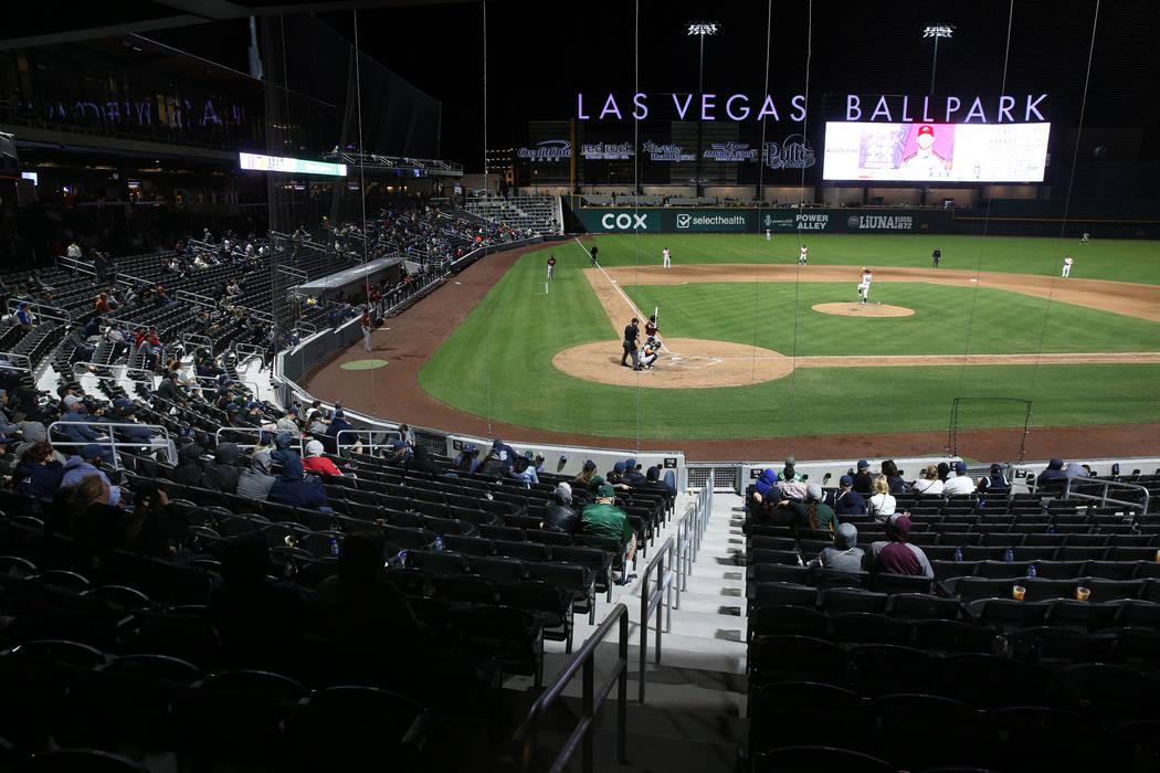 Los aficionados asisten a la acción durante la cuarta entrada en la noche de apertura de los A ...