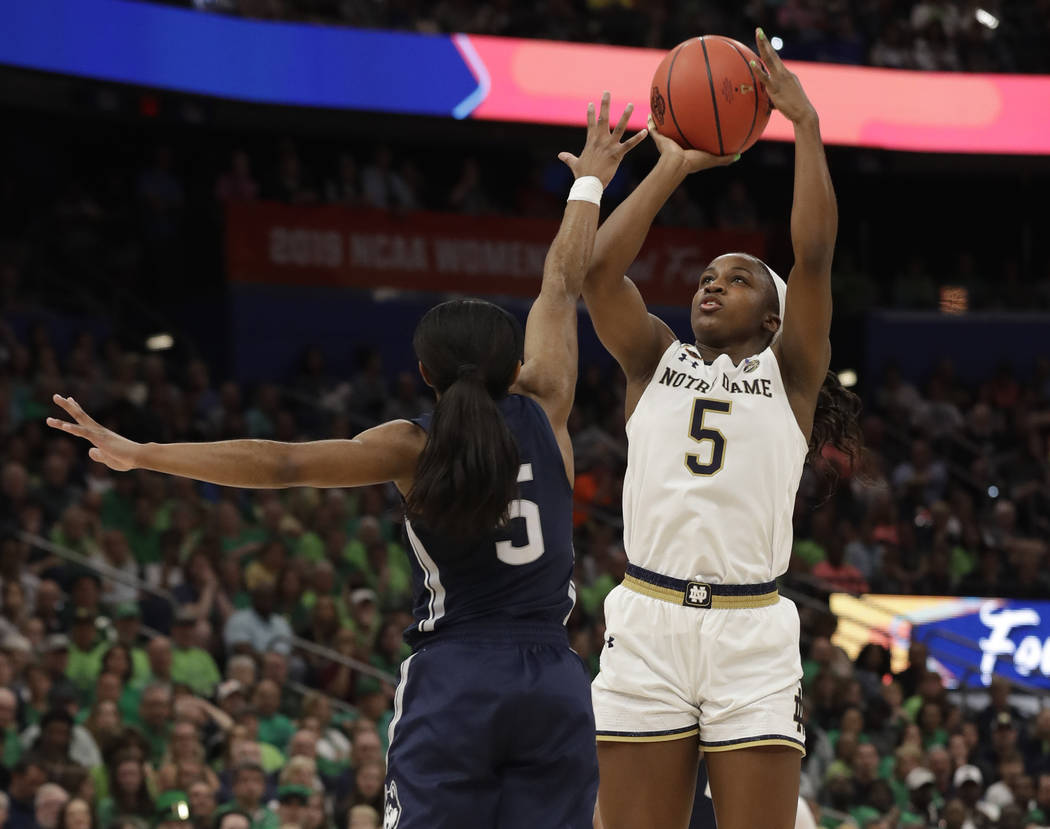 Jackie Young, defensa de Notre Dame, lanza el balón sobre Crystal Dangerfield de Connecticut, ...