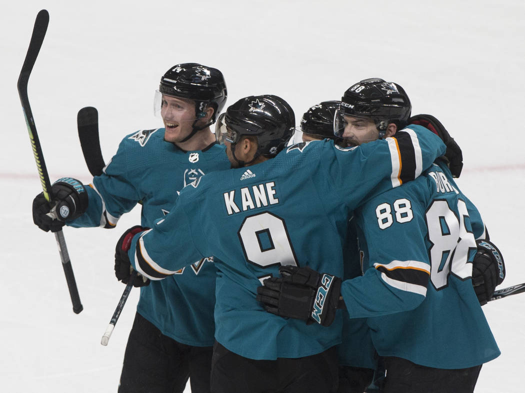 El ala izquierda de los San José Sharks, Evander Kane (9), celebra con su compañero de equipo ...
