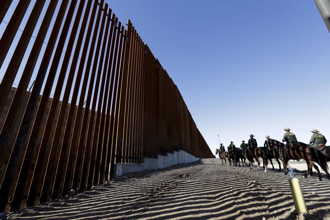 Agentes de la Patrulla Fronteriza montados a lo largo de una estructura del muro fronterizo rec ...