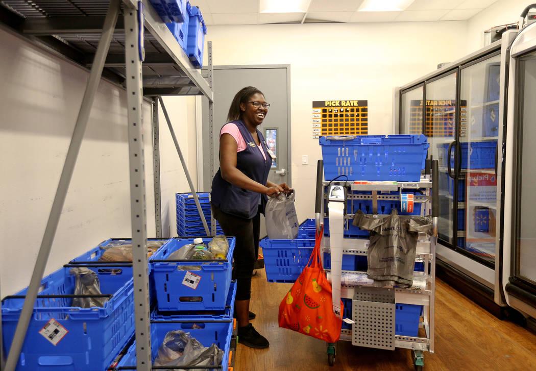 La Asociada Kiara D., de Walmart, prepara los carros para las órdenes de recolección en líne ...