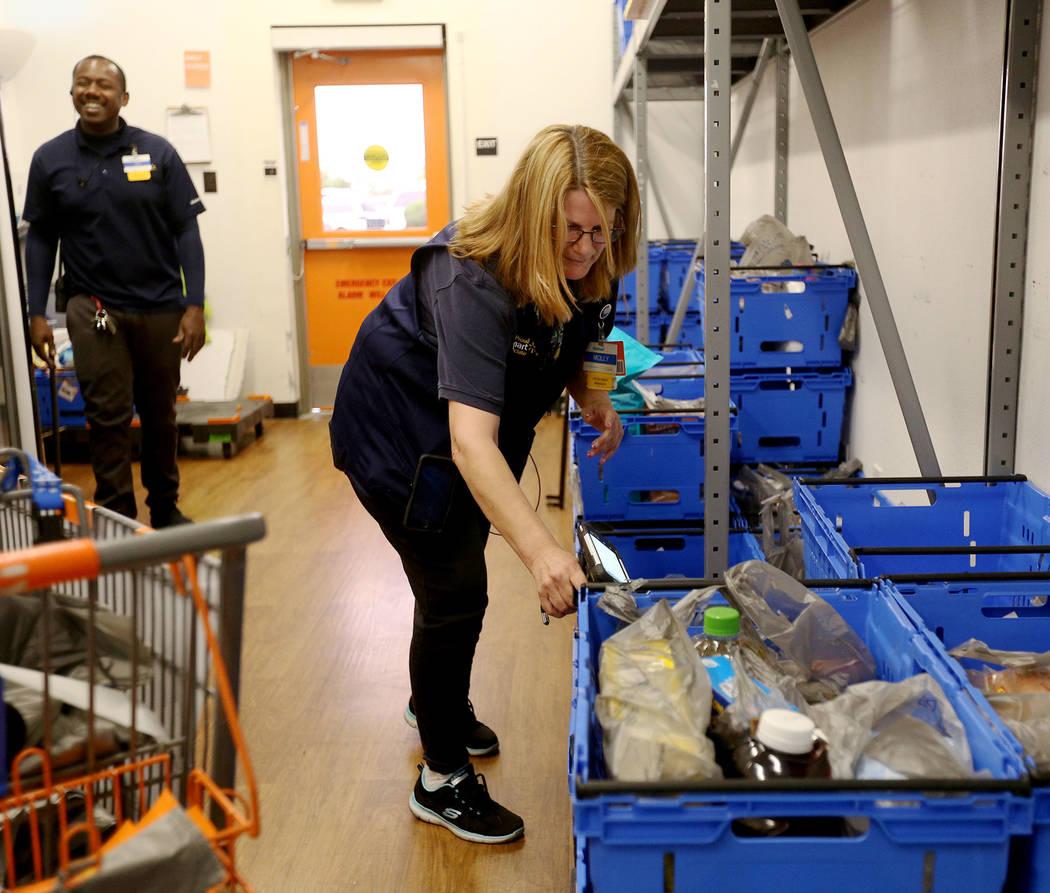 La Asociada Molly, de Walmart, prepara carros para pedidos en línea en la sala de recolección ...