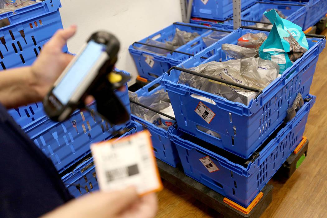 La Asociada Molly, de Walmart, escanea un carrito para una orden de recolección en línea en l ...