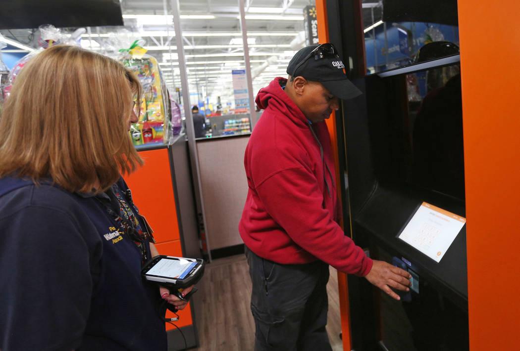 La asociada de Walmart, Molly, mira cómo Harold Lloyd busca su pedido en la torre de recolecci ...
