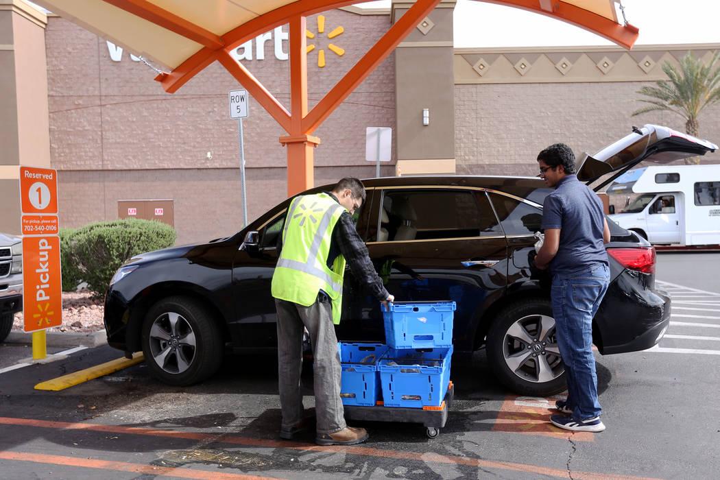El Asociado de Walmart, Dharian H., ayuda a Aditya Subramania, de 17 años, a cargar el pedido ...