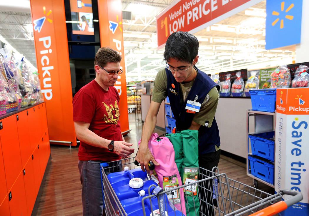 La asociada de Walmart, Molly Tye Bonilla, coloca los artículos en la tarjeta de Eric Viggiano ...