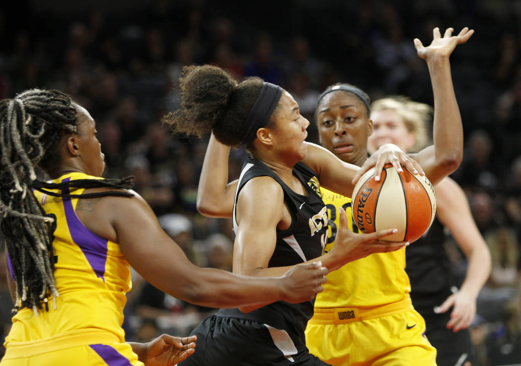 La alera de Las Vegas Aces, Nia Coffey (12), empuja el balón a través de la defensa de Los An ...