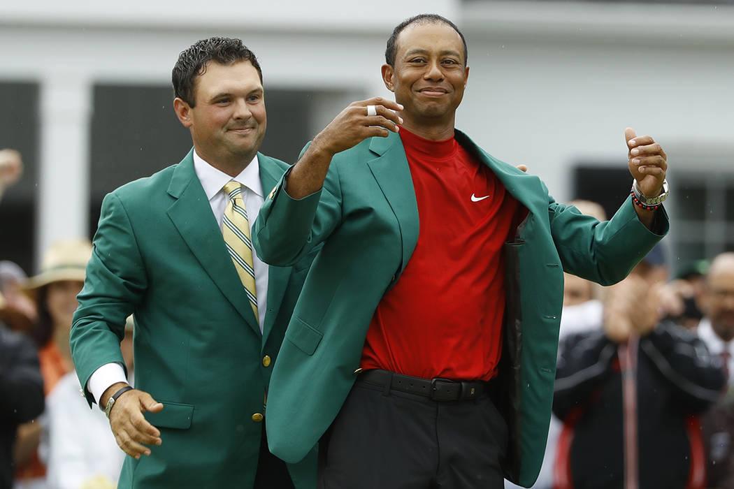 Patrick Reed ayuda a Tiger Woods con su chaqueta verde después de que Woods ganó el torneo de ...