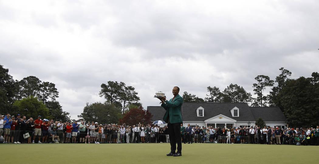 Tiger Woods sostiene su trofeo después de ganar el torneo de golf Masters el domingo 14 de abr ...