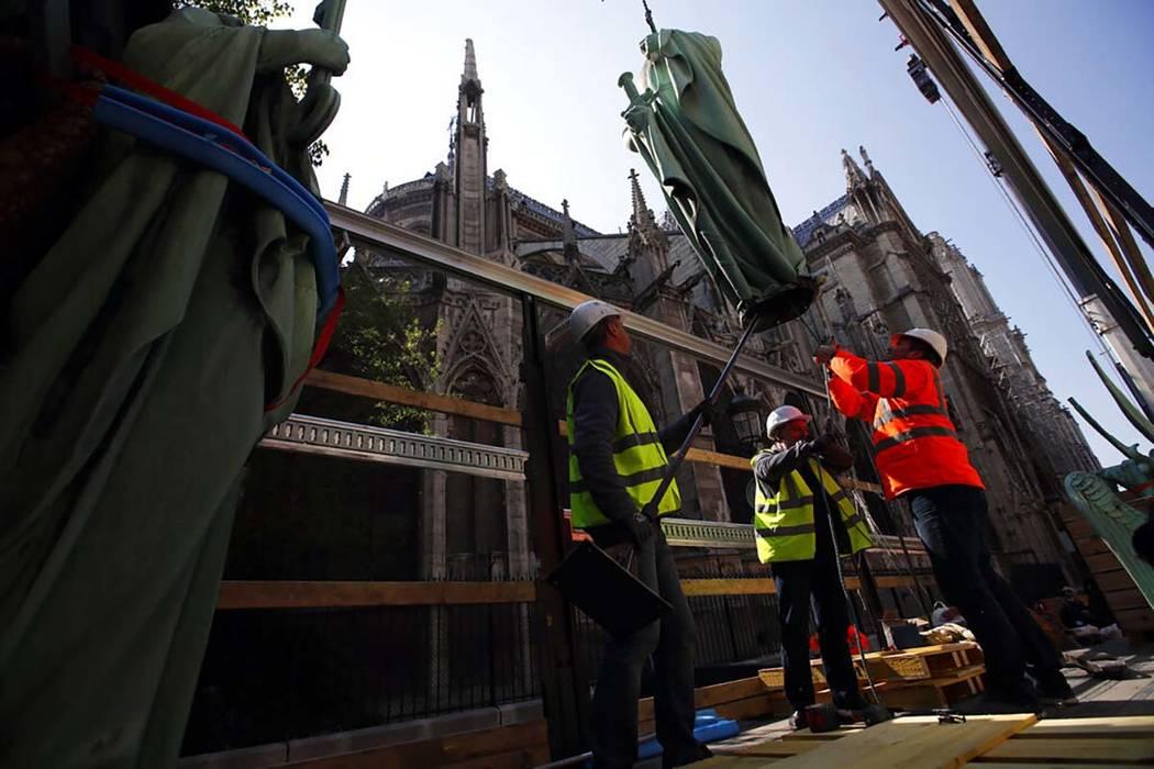 Los trabajadores aseguran una estatua religiosa posada en lo alto de la Catedral de Notre Dame ...